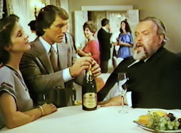 """""""Ahh, the French!"""" Orson Welles enjoys some wine."""